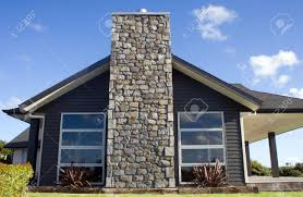 a modern home exterior with a stone chimney stock photo picture