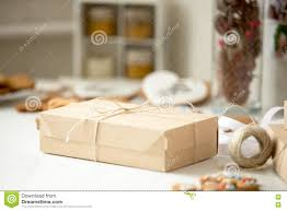 cardboard box postal parcel wrapped in brown kraft paper tied