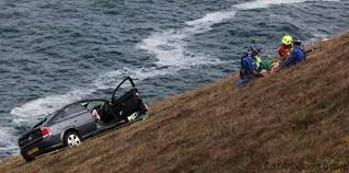 driver clings to cliff edge after rolling car