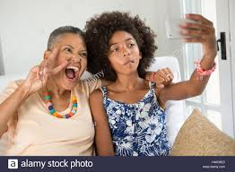 teaching grandmother how to take a selfie stock photo