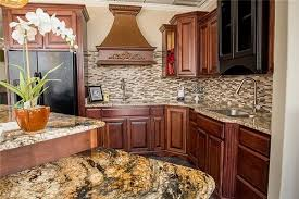 what backsplash goes with brown cabinets kitchen island with golden granite paired with
