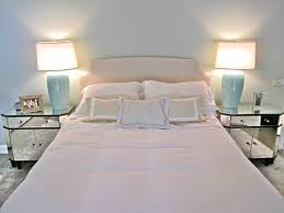 double mirror bed side table and white shade table lamp flanking