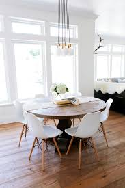Interesting Tables A Rustic Round Wood Table Surrounded By White Eames Dining Chairs