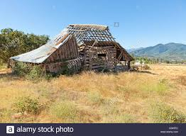 Farmhouse Ranch Old Dilapidated Barn Falling Apart In Field Of Farm Ranch In Stock