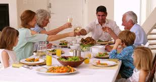 extended family saying grace before dinner at home in the dining