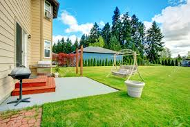 backyard small patio area with swing large green lawn with fir