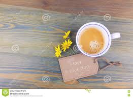 coffee cup and daisy flowers with wish cardboard label on wooden