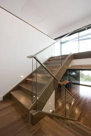 modern staircase with a glass balustrade and wooden handrails for