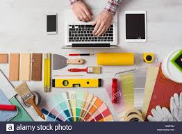 professional decorator s hands working at his desk and typing on a professional decorator s hands working at his desk and typing on a laptop color swatches paint rollers and tools on work table