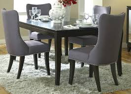 small solid wood dining room table and four grey upholstered high