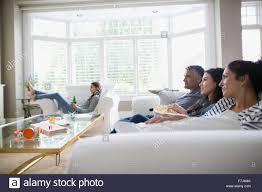 family watching tv on living room sofa stock photo royalty free