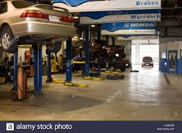 honda dealer cars a honda dealer has a busy repair shop with cars on hydraulic lifts