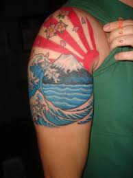 japanese sun rays and blue wave tattoos on shoulder tattoobite