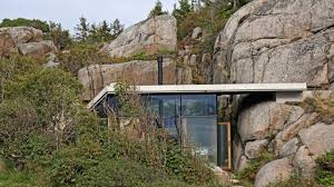 a modern cabin tucked into a rocky norwegian coastline lund