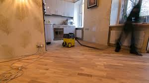 Vacuum Cleaners For Laminate Floors Carpenter Workers In Green Uniform Cleaning Room With A Vacuum
