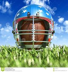 The Oval American Football Helmet Over The Oval Ball On The Grass Frontal