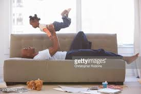 Father Lying On Sofa Holding Daughter Up Stock Photo Getty Images - Lying sofa 2
