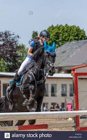 color matched horsewoman and black horse are jumping over the