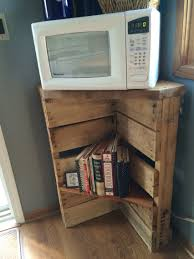 2 old doors transformed into a microwave stand with shelves we pallet microwave stand and cookbook shelf or possibly use in the garage for corner storage