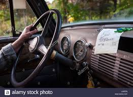 Vintage Ford Truck Steering Wheel - a driver has one hand on the steering wheel of an antique