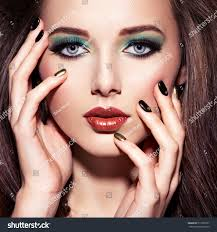 beautiul woman with green make up and creative color of nails