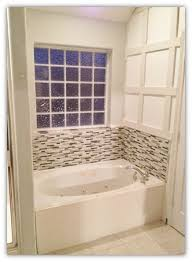white oval bathtub with mosaic pattern bathroom backsplash tile