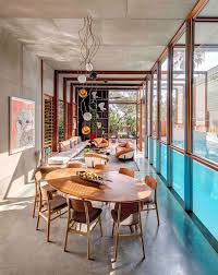 this new house was surrounded with screens to filter the light and sculptural lighting hangs from the ceiling above the oval dining set featured in this modern house