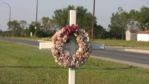 a white cross with a flower wreath hanging on it stand by the side