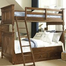 brown bunk bed with double beds and ladder also three