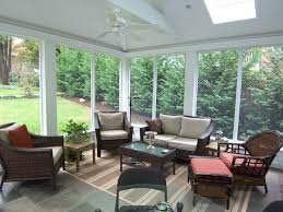 screened porch with stone floor skylight and ceiling fan land
