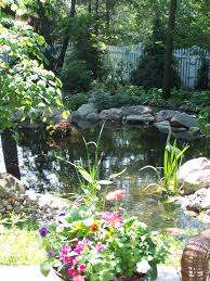 shade trees a pond and containers filled with flowers make for a
