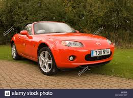 mx5 a red mazda mx5 sports car parked on a drive outside a house stock
