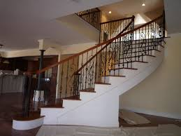cool curved staircase design with iron balusters and handrails