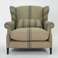 orange fabric wing back chair plus arm rest also cream wooden legs