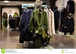 fashionable women dress on hangers in clothing shop stock photo