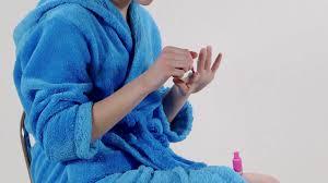 teen wearing blue bathrobe painting nails with pink nail