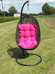 black wicker hanging swing chair with pink cushion and round black