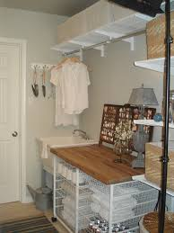 organizing small laundry room after makeover with white interior