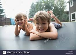 portrait smiling boys laying on trampoline in backyard stock photo