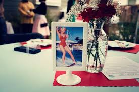 i love this s housewifethemed bridal shower  offbeat bride with the centerpieces kill me simple flowers next to a framed pinup photo  really set up the whole sexy girly goodtimes mood from offbeatbridecom