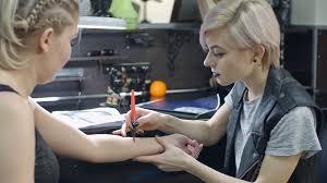 female tattoo artist drawing tattoo sketch stock video footage