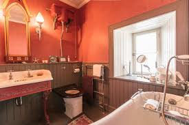 victorian bathroom with red walls and fireplace creating a rich