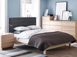 a bedroom with oppland bed chest of drawers and bedside table in