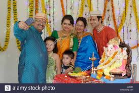 indian family in traditional celebrating ganesha festival