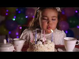 little blowing out the candles of birthday cake stock