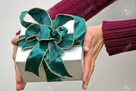wire edged ribbon are holding a gift of a white box and green wire edged