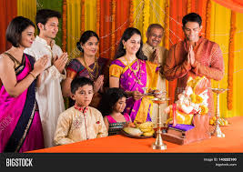 Decoration For Puja At Home by Cheerful Indian Family Celebrating Or Praying Lord Ganesh Or