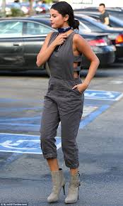skin jumpsuit selena gomez shows some skin in cut out grey jumpsuit and towering