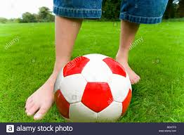 barefoot playing soccer in grass stock photo royalty free