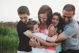 candid portrait of happy loving family with teenagers hugging